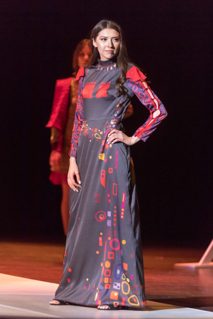 Model wearing a long, multicolored gown.