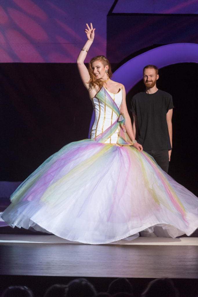 Model wearing an elaborate, billowing white, green, yellow, and purple dress.