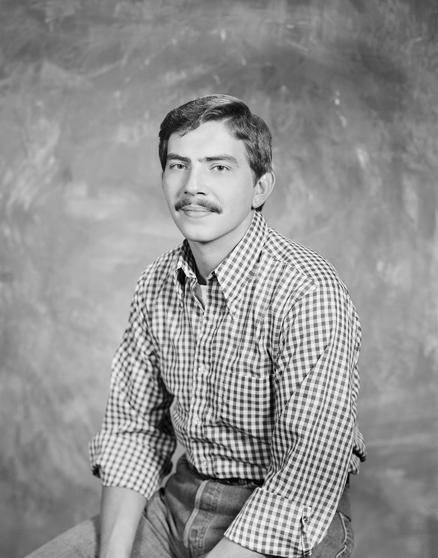 A man in a plaid shirt with a mustache smiling in front of a studio backdrop in black and white.