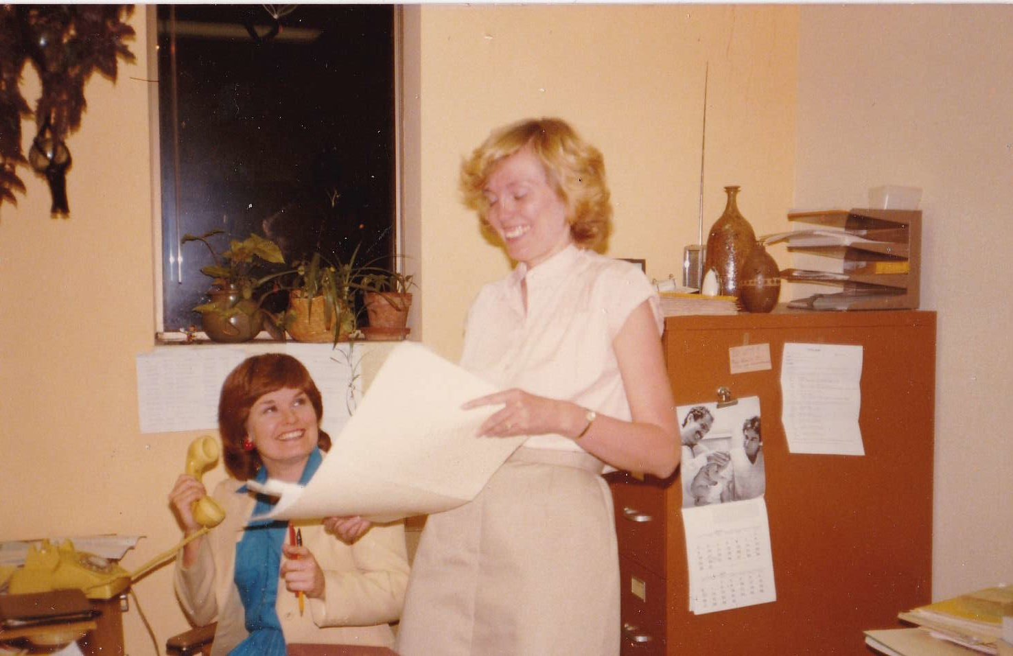 Two women smiling and working in an office. One is holding an old phone, the other a folder of papers.