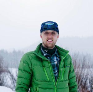 Man standing in winter gear in front of a snowy mountain scene.