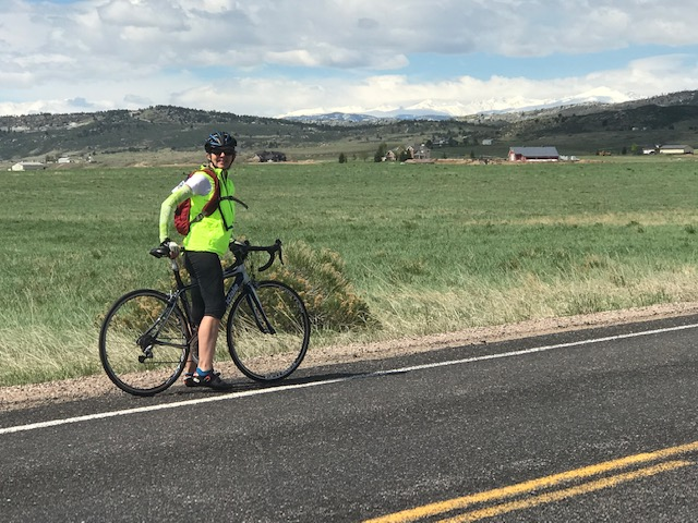 Barb enjoying a bike ride with mountain views