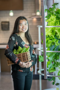 Kiri Michell harvests produce from the Tower Garden, an aeroponic garden unit.