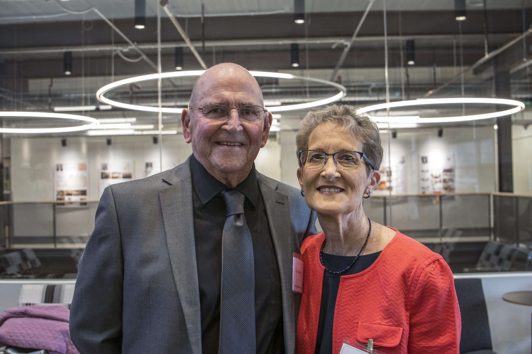 A woman and man dressed nicely smile in front of a modern looking interior.
