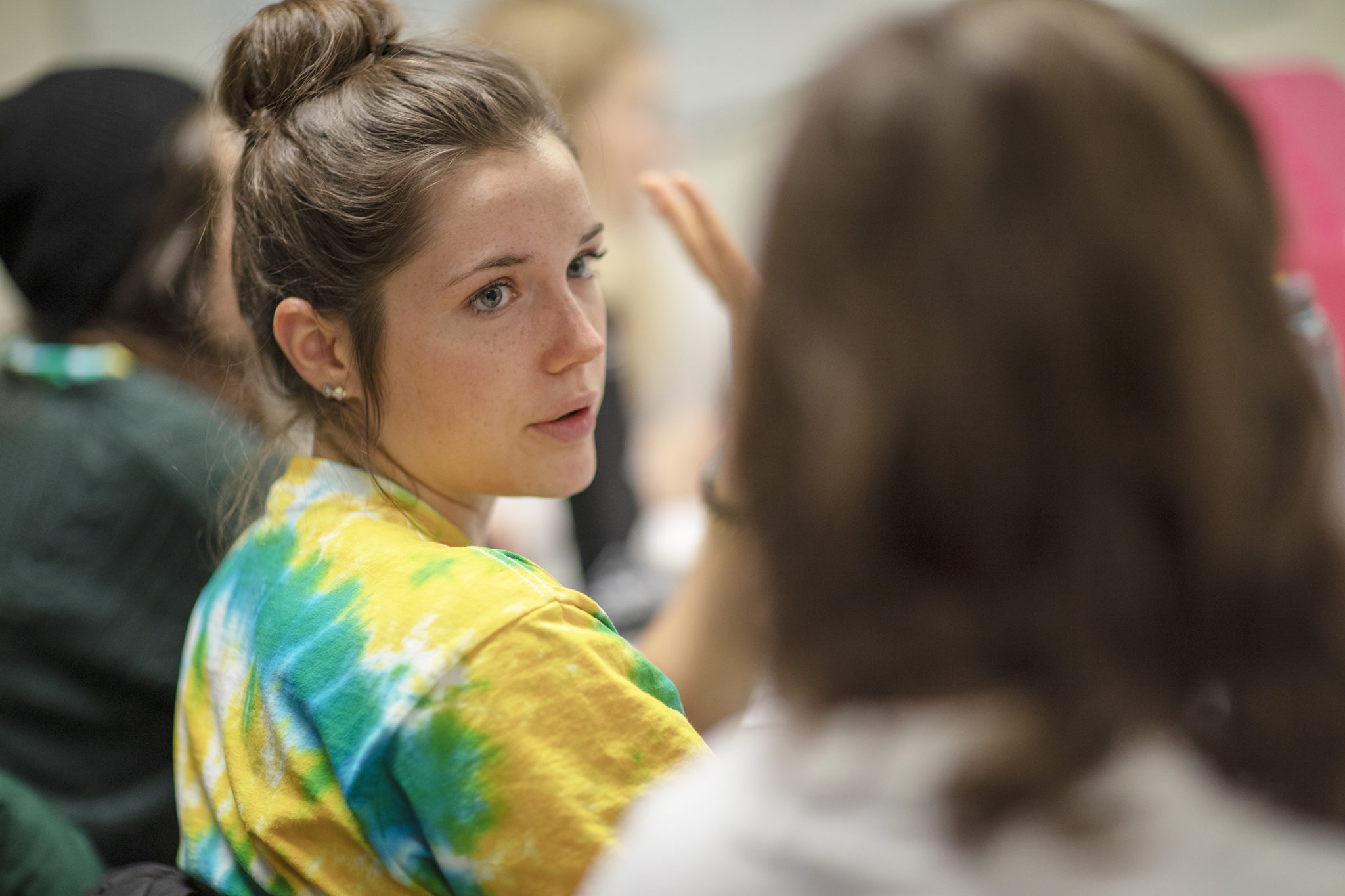 A female student in a tie-dye t shirt works with youth.