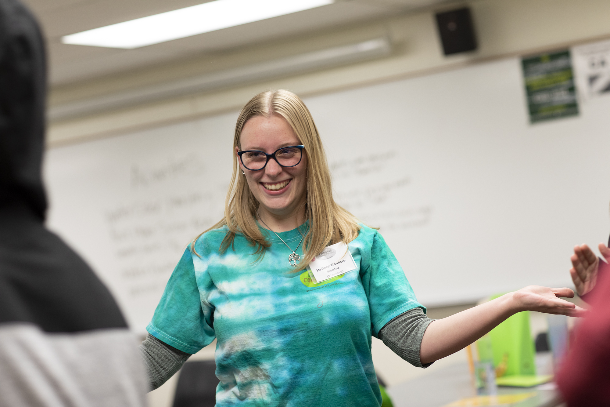 A blonde female student in a tie-dye t shirt works with youth.