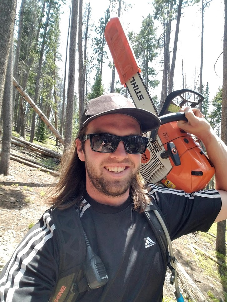A selfie of a man with long hair and beard smiling and holding a chain saw in the woods.