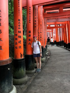 Grayson standing among red Japanese arches.