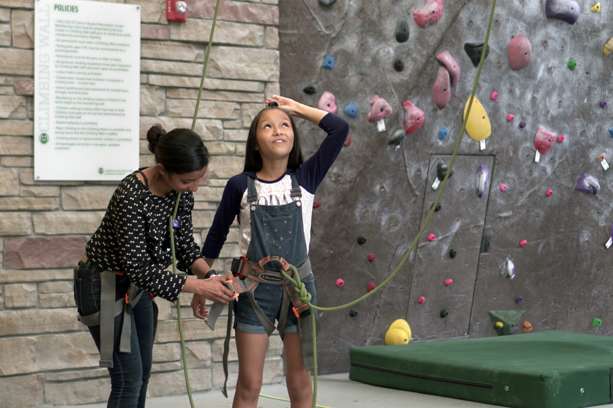 A young girl looks excitedly upward after climbing an indoor rock wall.