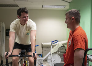Ewell talking with research participant who was doing bike sprint interval training.