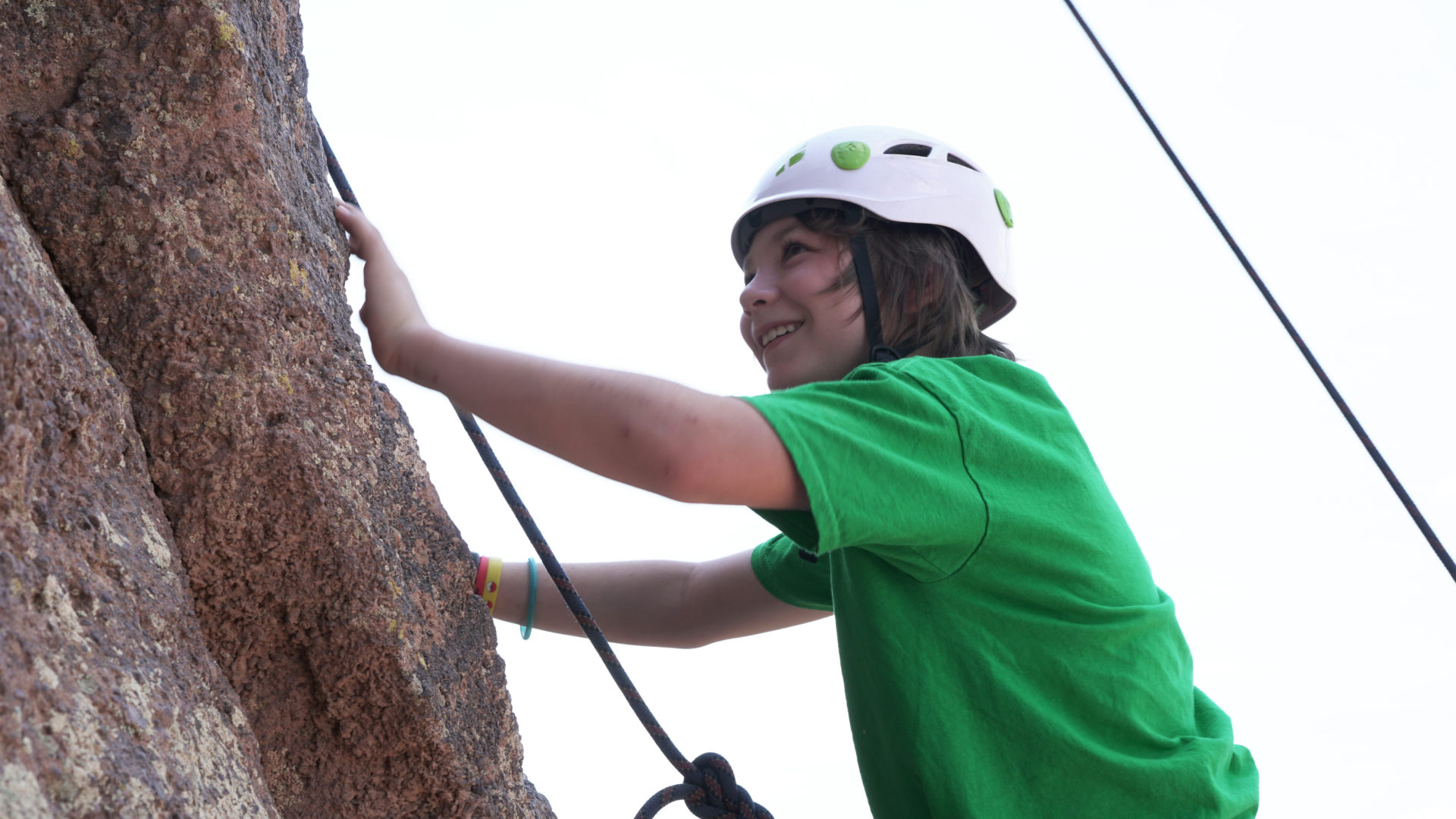 Young boy climbs a rock in a green shirt.