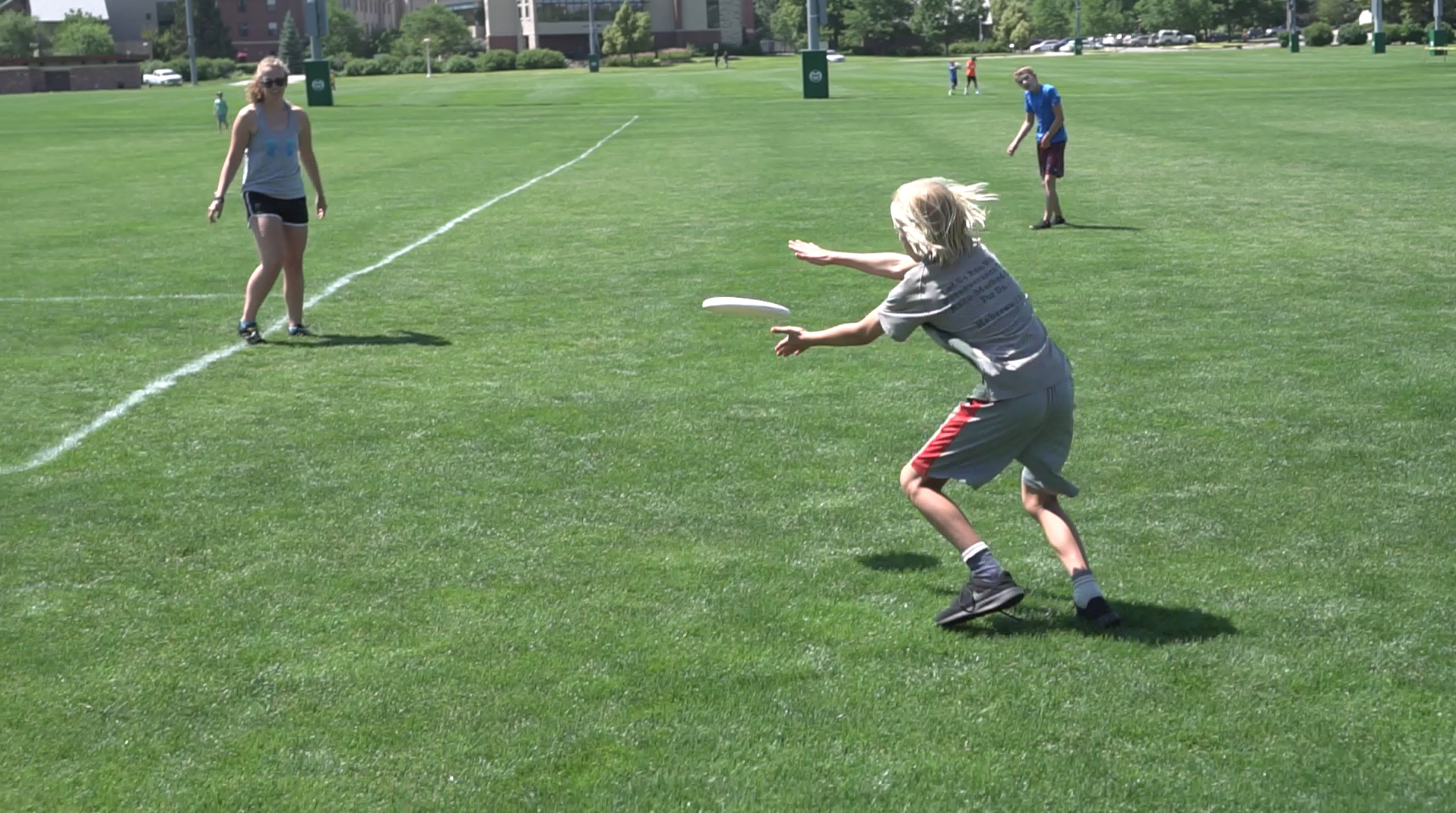 A boy catches a frisbee on a field