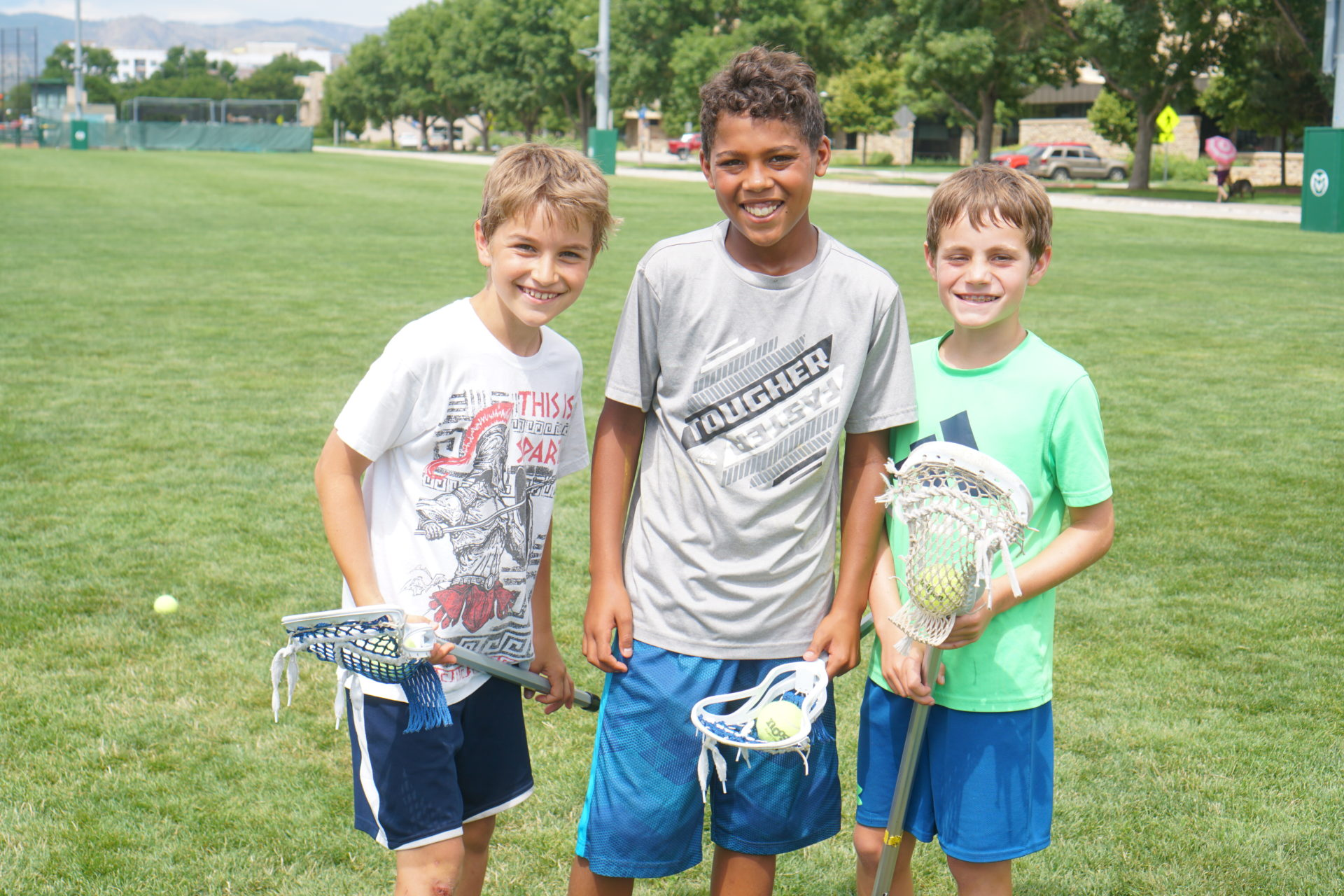 Three boys smile on a lacrosse field with lacrosse sticks.
