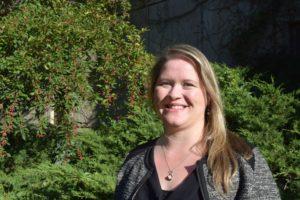 Kristen Morris standing in front of greenery.