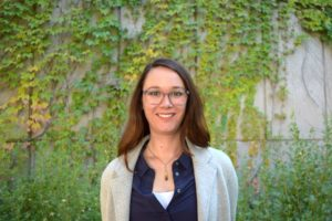 Megan Mueller standing in front of greenery.