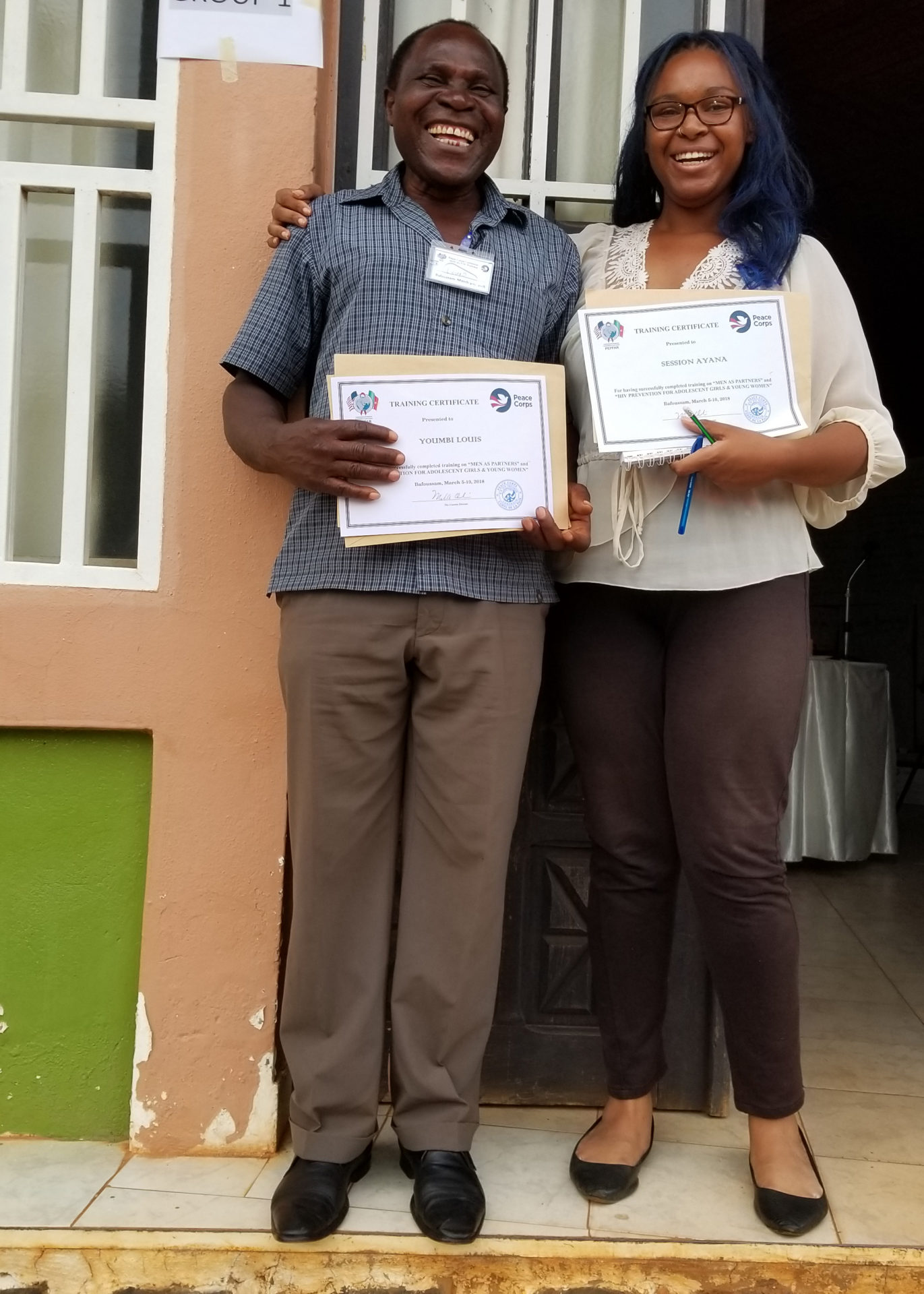 Ayana Session standing with a local chief with certificates of completion for attending a gender and violence training together.