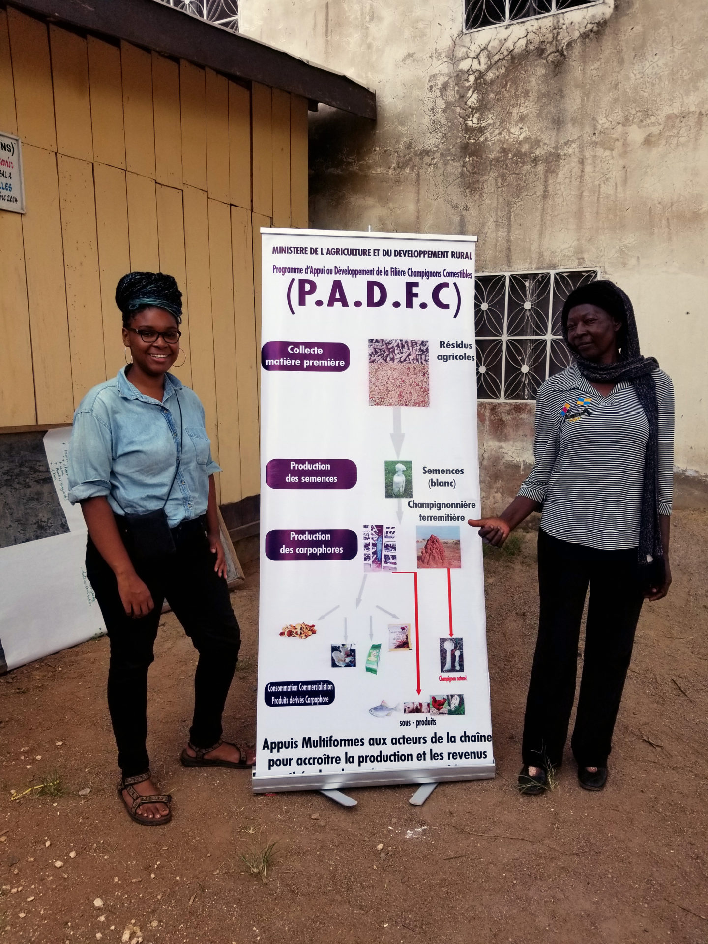 ayana session attending a mushroom growing conference. she is standing with a fellow attendee in front of conference signage