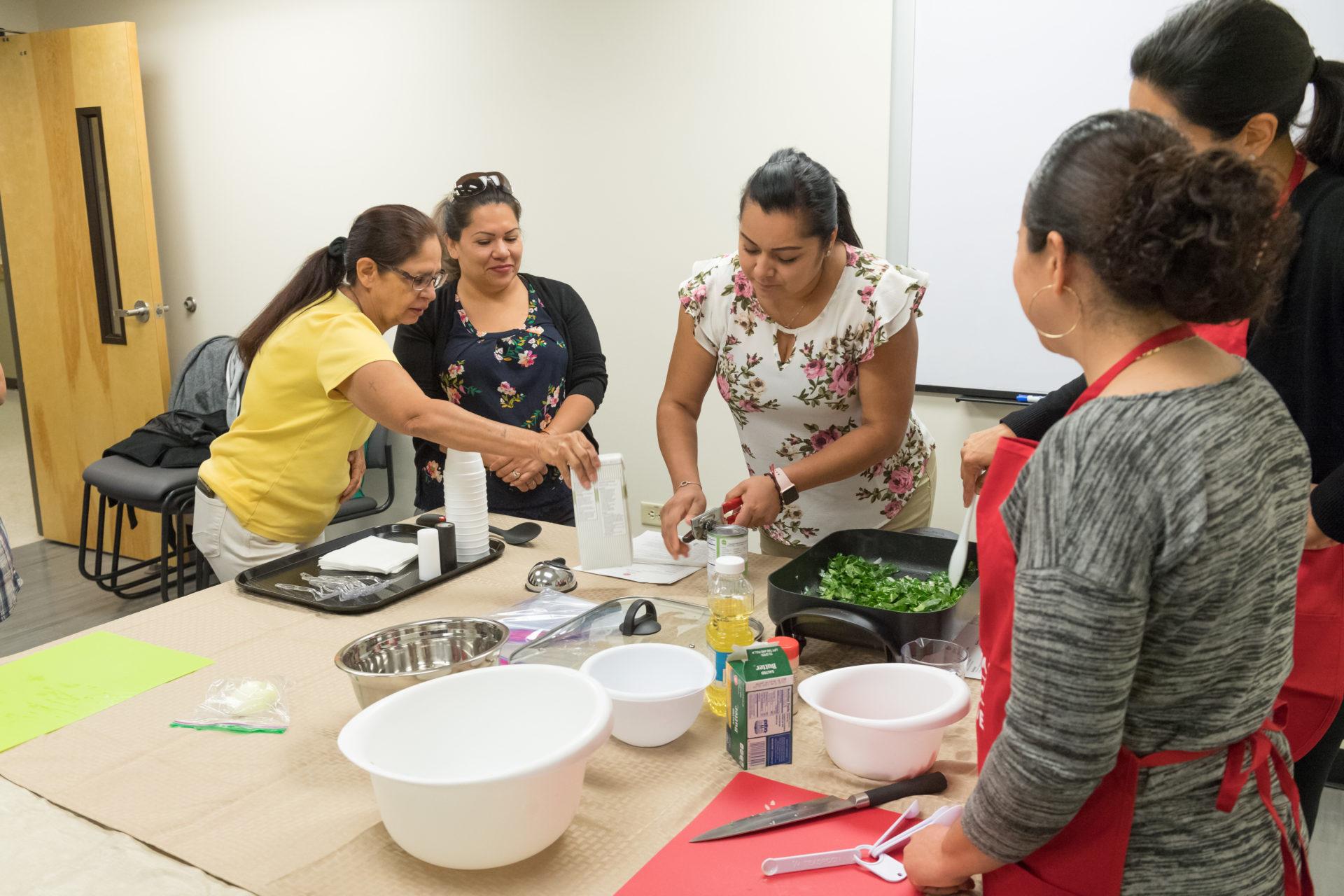 Women gather around a food preparation demonstration.