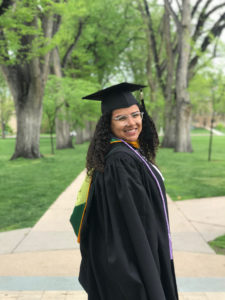 Lucy Delgado stands on the Oval at Colorado State University, wearing graduation cap and gown