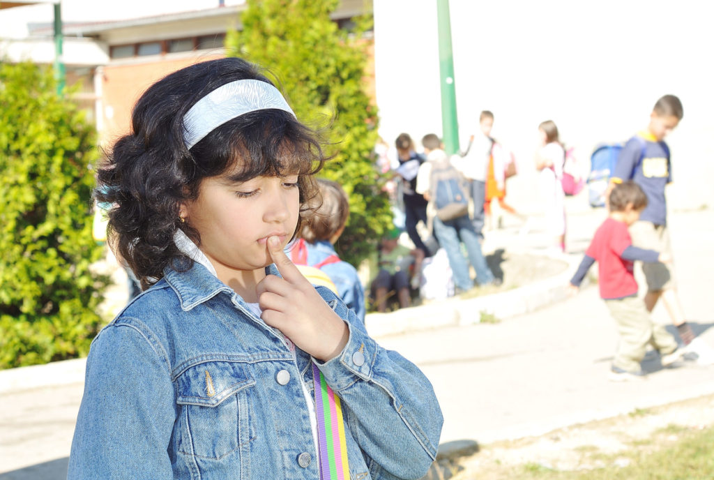 a child in front of elementary school with an uncertain look on her face