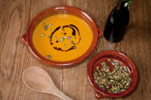 A bowl of pumpkin soup and a side of roasted pepitas