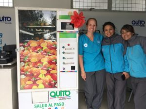 Jenni Averett with others at a fruit vending machine.