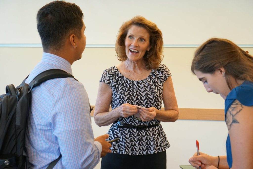 Dr. Wendy DeYoung talks to students while they wait for their turn to speak to panelists