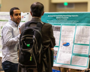 Abdo Abdallah showing poster to male attendee
