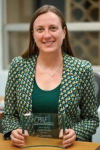 Zarestky holding her award and smiling.