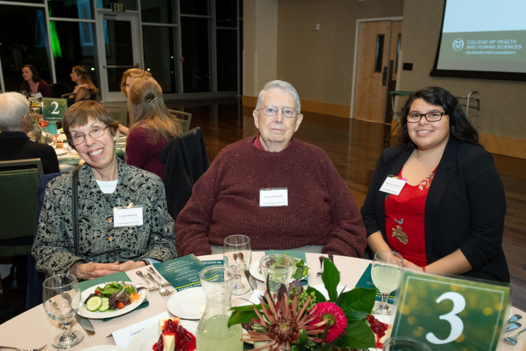 Student and her two scholarship donors smiling at the dinner table in a group photo.