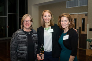 Peggy Walsh holding her award standing with Lise Youngblade and Wendy DeYoung smiling