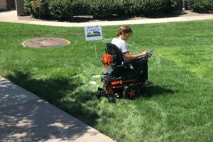 A woman tests a wheelchair's ability to function in grassy terrain.