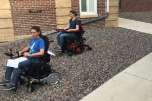 Two participants test wheelchairs in a gravel pit.