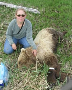 Anne Welch outside kneeling next to a bear.