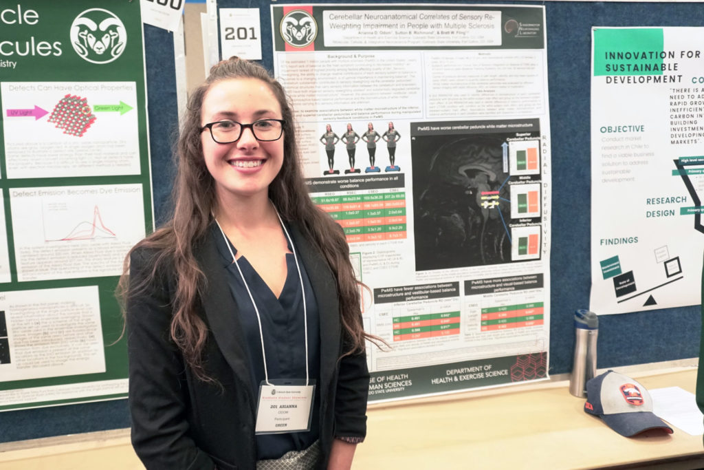Arianna Odom smiling in front of her research poster.