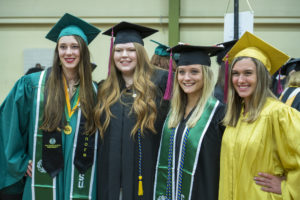 Four students in graduation regalia.