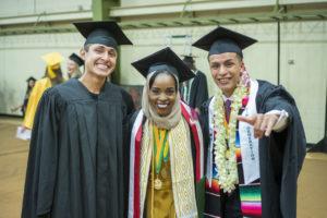 Three students in graduation regalia.