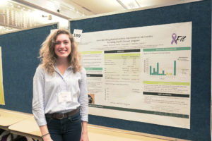 Emma McGinnis smiling in front of her research poster.