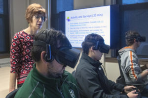 Olbina instructs students in the use of VR.