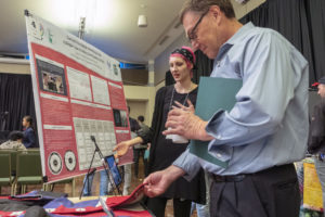 Attendee looking at Kayna Hobbs' research.