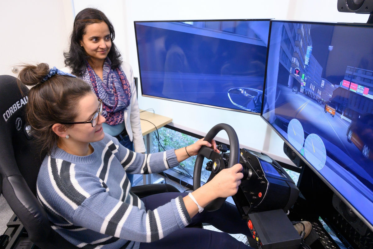 Neha observes student participating in the driving simulation.