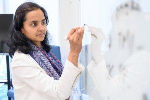 Dr. Neha Lodha writing on a white board.