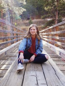 Shelby Taylor sitting on a bridge smiling for profile picture.