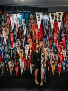 Two female students stand in front of college banners.