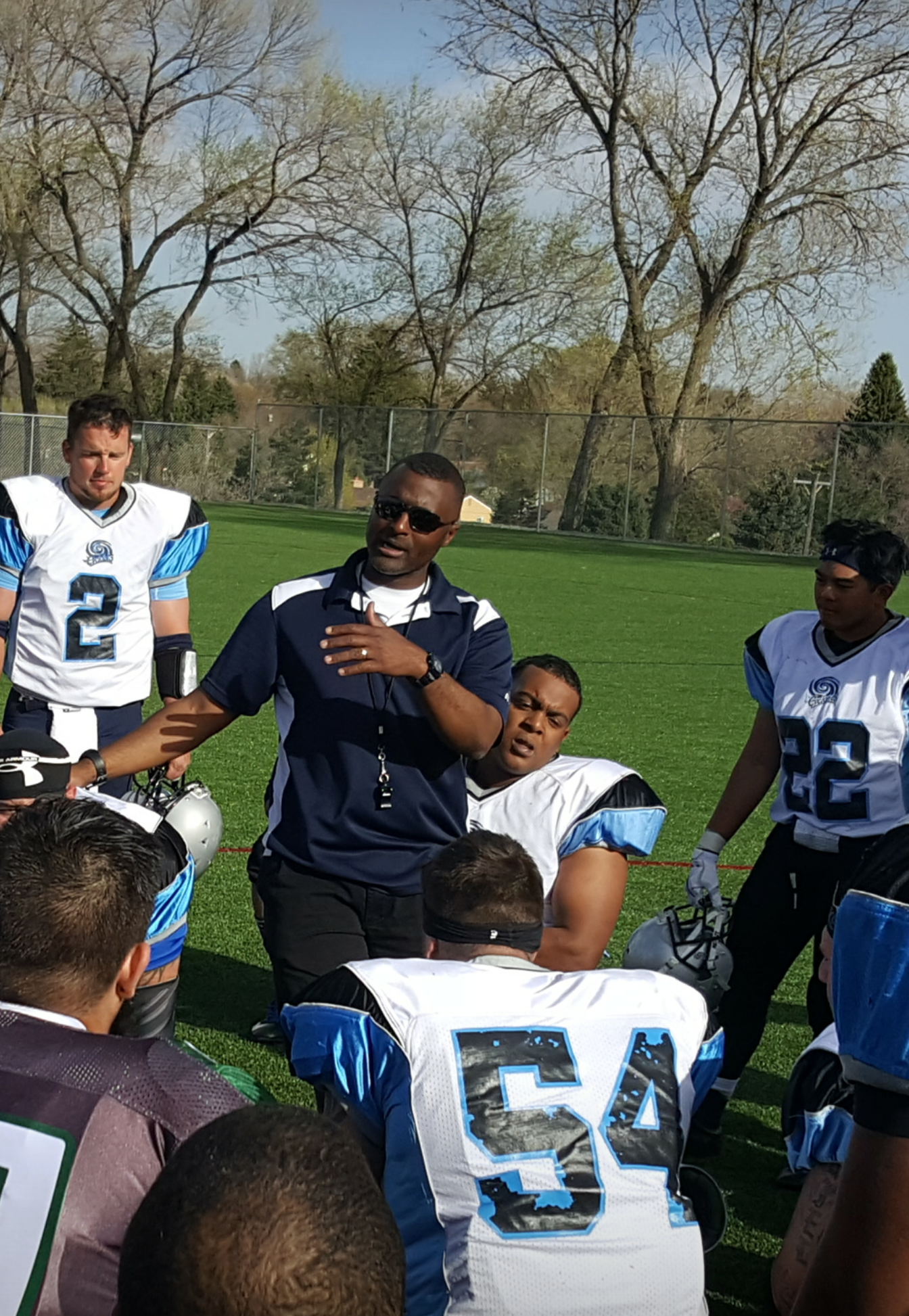 Rainey stands on a foot ball field with players.