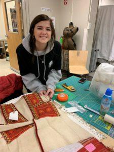Undergraduate Student, Ashley Stem sewing on labels.