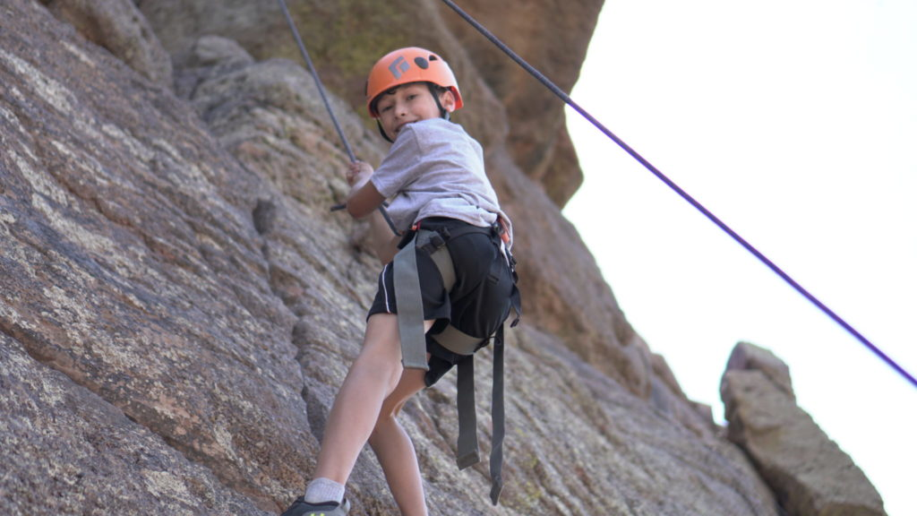 A boy smiling while rock climbing