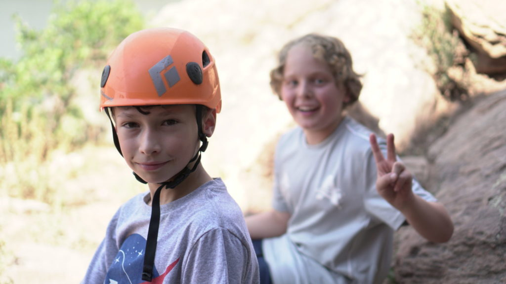Two boys smiling at rock climbing outing