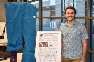 Nick Koch smiling in front of his ski wear project