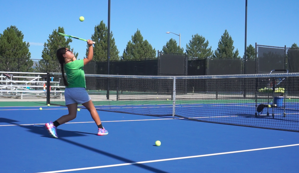 Girl hitting a tennis ball on a court
